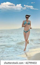 The girl running on seacoast. The European appearance in sunglasses