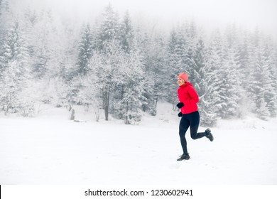 Girl running on snow in winter mountains. Sport, fitness inspiration and motivation. Young happy woman trail running in mountains on snow, winter day. Female trail runner jogging outdoors.