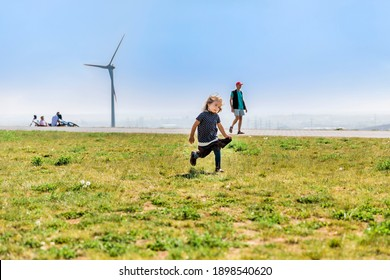 Girl running on top of hill with wind turbine and man in background