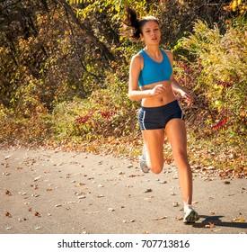 Girl running in park woods on trail