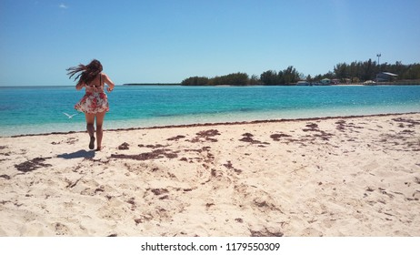 Girl running to the sea, on a beach in Bimini, The Bahamas