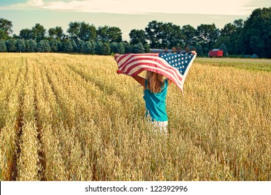 girl running with wheat field with American flag