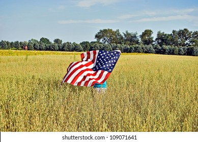 girl running in wheat filed with a flag