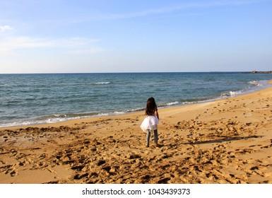 girl runs along the beach