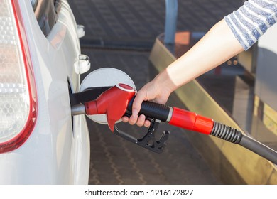 the girl runs the car at the gas station. close up.