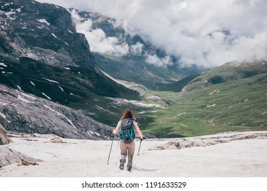 A girl runs and jamp down a snowy slope towards the green valley