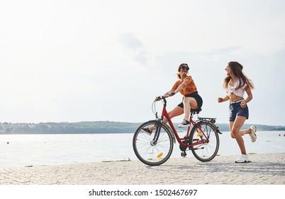 Girl runs near bicycle. Two female friends on the bike have fun at beach near the lake.