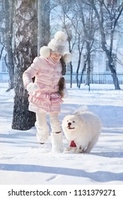 a girl runs and plays with a samoyed dog in the snow
