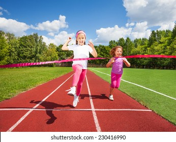 Girl runs and reaches ribbon excited to win the marathon and second girl runs behind