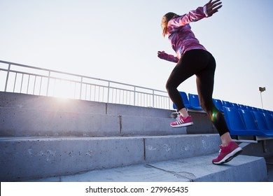 Girl runs upstairs to a sunset. Young woman in sportswear training on a stadium. Copy space. Healthy lifestyle in a city concept
