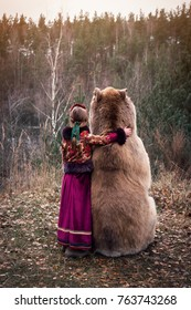 A girl in the Russian national dress hugging a real brown big bear. Lte autumn period in the forest