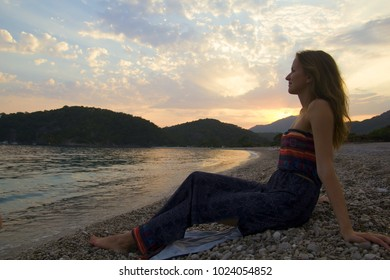 Girl in rustic off the shoulder dress sits on the sea beach. Beautiful sunset at the seaside with mountains on background. A stream of light in evening sky. Gorgeous woman silhouette. Ocean beach