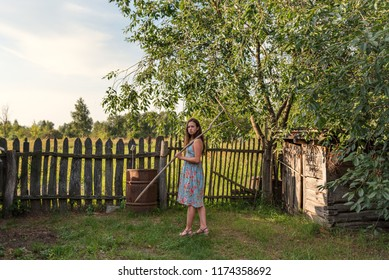 a girl in a rustic old-fashioned dress goes holding a rake over a rural garden courtyard