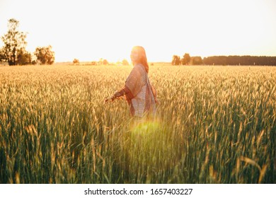 girl in rye at sunset. summer and woman in running on field