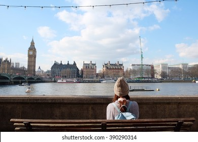 A girl 's sitting beside Thames river, watching London city Big Ben and Westminster bridge