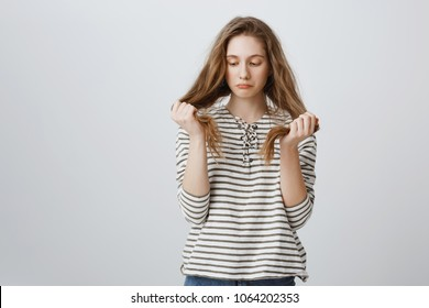Girl is sad of her bad hair strands. Portrait of gloomy bothered young woman holding hair and being upset, having split ends, needing help of hairdresser or new haircut, standing over gray wall