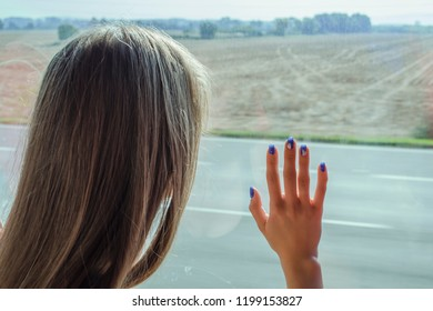 The girl is sad, looks out the window with a hand to the glass leaves hometown