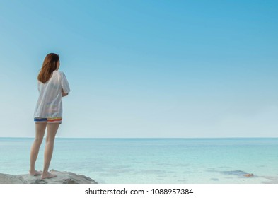 A girl is sad that stand on the stone look forward which has the sea and sky on a lonely day