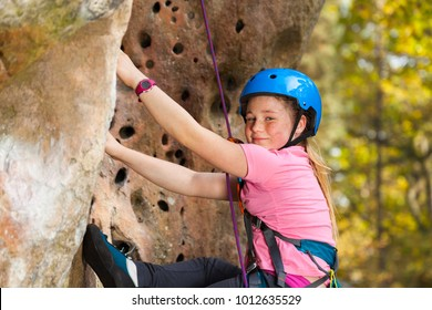 Girl in safety helmet climbing on the rock route