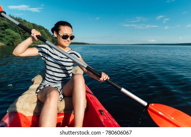 the girl sails on a kayak, paddles with a paddle.