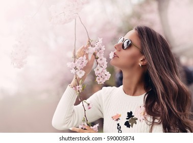 Girl with sakura tree flowers. Focus on face. Spring concept