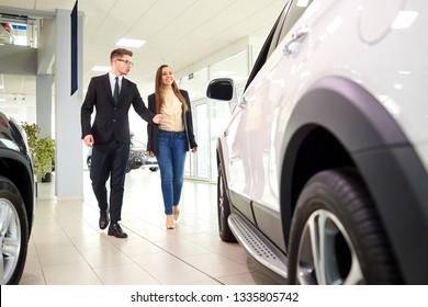 Girl and the salesman choose a car in the auto showroom