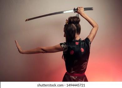 Girl with samurai sword studio shot