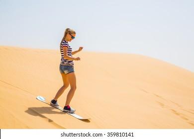 Girl sand boarding in a desert and having fun