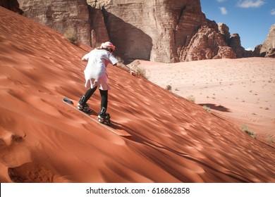 Girl sand boarding on dunes in Wadi Rum, Jordan