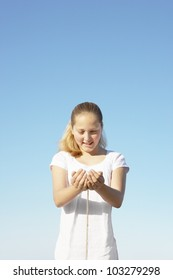 Girl with sand filtering through her hands against a blue sky.