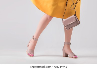 A girl in sandals with a heel and a bag in her hand. Fashionable kit of handbag and shoes.