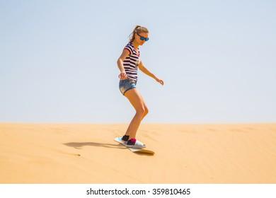 Girl sandboarding in a desert in South America
