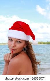 Girl in santa claus hat on tropical beach, caribbean sea