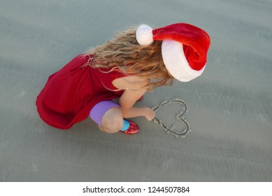 Girl in a Santa hat drawing a heart in beach sand
