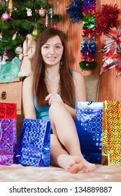 Girl in Santa hat sits with christmas gifts