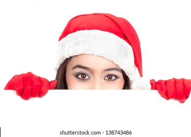 Girl in Santa peeking over paper sign board. Cute funny photo closeup of christmas woman with copyspace. Isolated on white background.