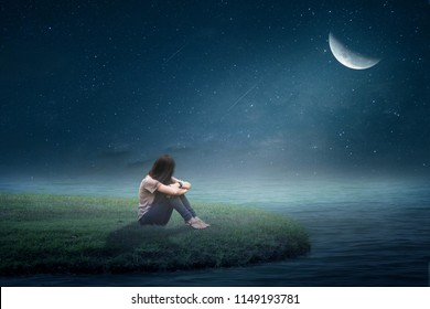 The girl sat in the grass in the middle of the moon half a lonely.