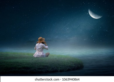 The girl sat half-moon in the grass in the middle of the water in a lonely night.