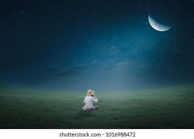The girl sat in the lawn in the moonlight half moonly.