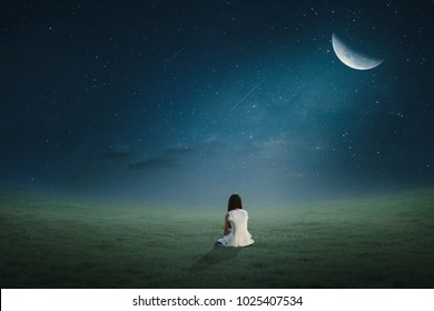 The girl sat in the lawn at night under a half-lonely moonlight.