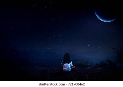 The girl sat on the cliff, looking half moon in the night with beautiful stars.