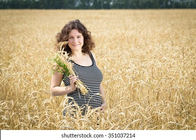 Girl saunters in the field with wheat. Girl is pregnant. She is very happy.