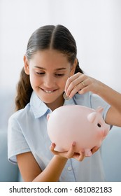 Girl saving a coin in piggy bank