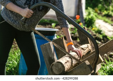 Girl is sawing a wooden beam the hand saw in the garden