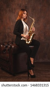 girl with a saxophone in her hands, near the chair. In full growth. Stylishly dressed