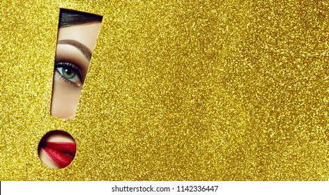 The girl says - attention A girl with beautiful puffy lips, painted in red lipstick with a metallic effect. Lips in the pit in the form of an exclamation mark of golden shiny paper.Fashion, beauty.