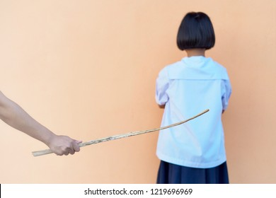 Girl scared of father's physical punishment with wood in hand..