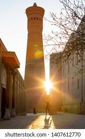 A girl in a scarf in front of Great Minaret of the Kalon and Kalon Kallan Mosque. Bukhara, Uzbekistan, Central Asia.