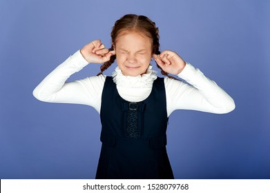 The girl in a school dress and blouse closed her eyes and covered her ears with her fingers. Reluctance to hear and see. Frustration. Quarrel with a teenager.