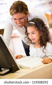 Girl at school with her teacher learning to use technology